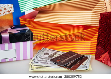 Close view ar colorful paper shopping bags and boxes with money and debit cards against blue background - stock photo