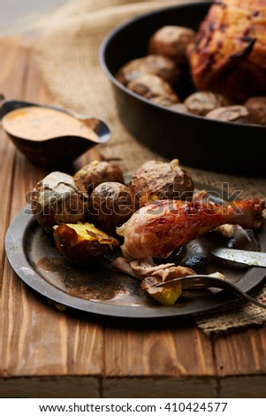 Close view at barbecued chicken leg with baked potatoes on a rustic metal plate with whole chicken and sauce on a background. Sackcloth and wooden background. Vertical shot. Warm colors - stock photo