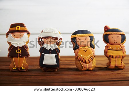 Close view at figures of gingerbread pilgrims and indians on a wooden background - stock photo