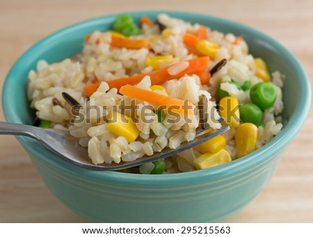Close view of a bowl of brown and wild rice with peas, carrots and corn with a fork filled in the foreground illuminated with natural light. - stock photo