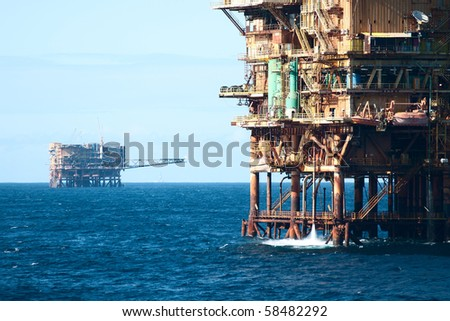 close view of a oil rig with another far on horizon - stock photo