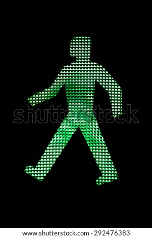 Close view of a pedestrian traffic light green man. - stock photo