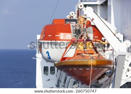 Close view of a rescue boat and a lifeboat hanging on a side of a cruise liner. - stock photo