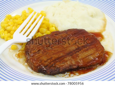 Close view of a Salisbury steak meal with corn and potato on a blue striped plate with white fork. - stock photo