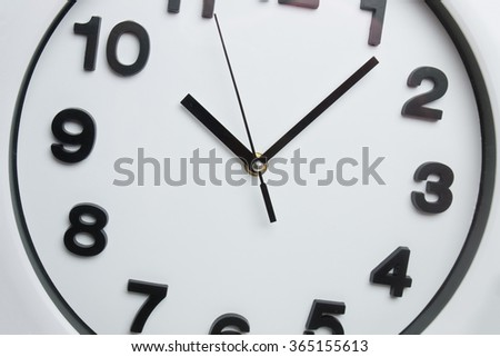Close view of a white kitchen clock with black numbers. - stock photo