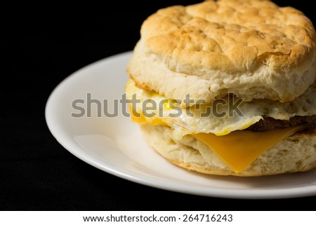 Close view of an sausage egg and cheese biscuit breakfast sandwich on a white plate upon a black fabric background. - stock photo