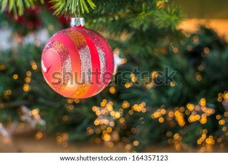 Close view of beautifully lit red christmas ball on tree branch. - stock photo