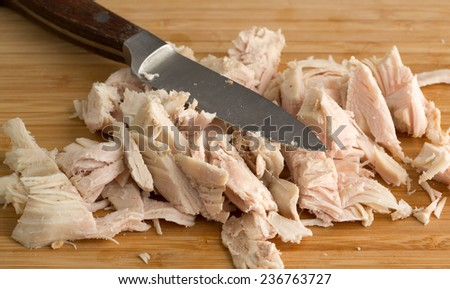 Close view of chopped turkey on a wood cutting board with a knife. - stock photo