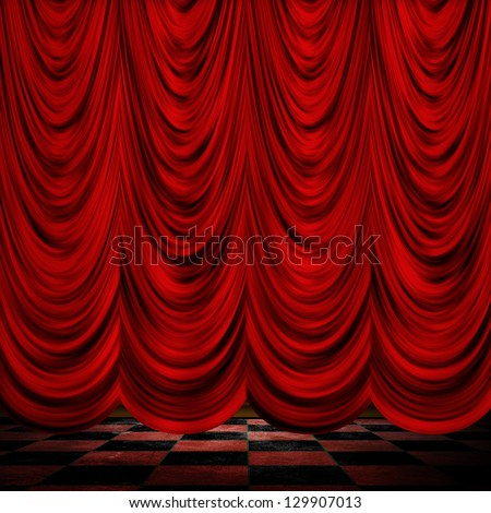 Close view of decorative red theater stage curtains with checkered floor. - stock photo