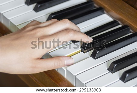 Close view of  girl's left hand holding pressed  keys on a piano - stock photo