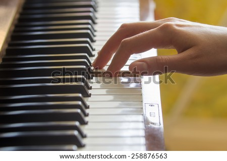 Close view of  girl's right hand's finger holding pressed A note key on a piano - stock photo