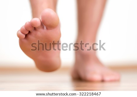 Close view of male feet making a step over home-like background. - stock photo