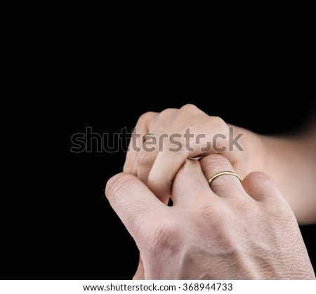 Close view of man's and woman's hands with wedding rings in a black background - stock photo