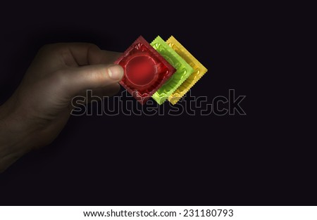 Close view of man's hand with 3 condoms packs - red, green, yellow - stock photo