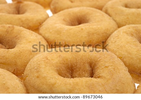 Close view of several fresh plain doughnuts very close together. - stock photo