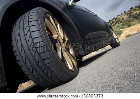 Close view of the wheel of a black sport car with the asphalt at foreground. Wheel. - stock photo