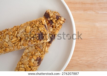 Close view of two chocolate chip granola bars on a plate atop a wood table top. - stock photo
