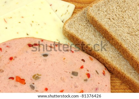 Close view of two slices of wheat bread, pickle and pimento luncheon meat and slices of pepper jack cheese on a wood cutting board. - stock photo