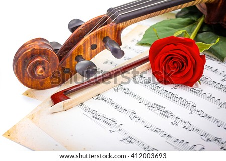 Close view of violin scroll, bow and red rose on musical sheet - stock photo
