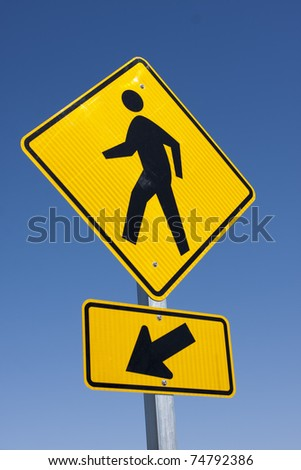close view of yellow and black pedestrian walkway sign agianst a blue sky - stock photo