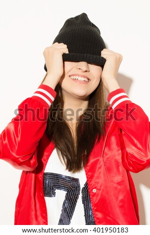Close your eyes. Young stunning female pulling her hat on eyes at the studio. - stock photo
