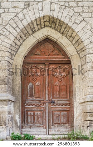 Closed ancient weathered arched church door - stock photo