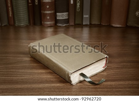 Closed book on the writing table - stock photo