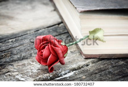 closed book on wood desk with rose - stock photo