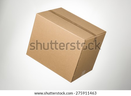 Closed cardboard box taped up on grey gradient - stock photo