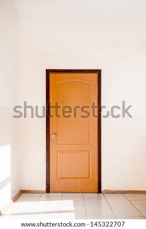 Closed door in empty hallway - stock photo