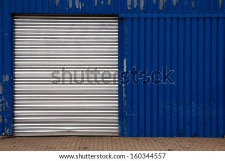 Closed door on a worn blue industrial metal shed at a shipyard in Hamburg, Germany. - stock photo