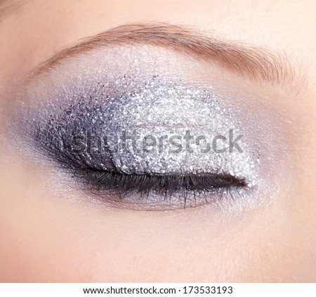 Closed eye of young woman with vogue shining sparkle makeup - stock photo