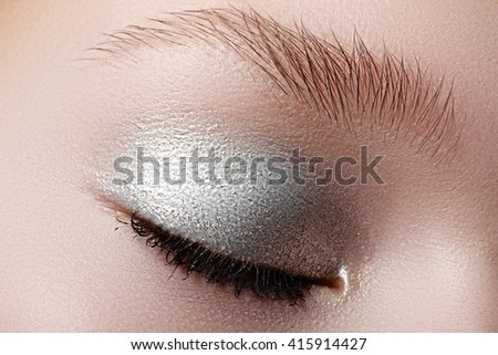 Closed eyes of young woman with shining sparkle makeup. Closeup image of beautiful woman eye with fashion makeup. Cosmetic Eyeshadow.