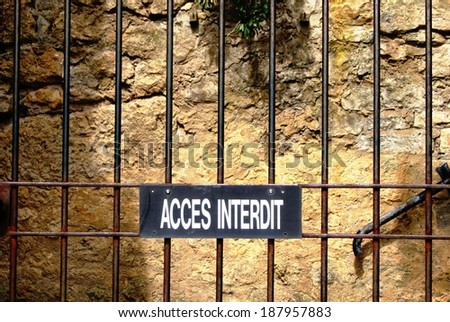 Closed fence with a sign mentioning Restricted Access in French - stock photo