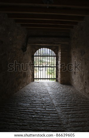 Closed gate at the end of a tunnel in an ancient Byzantine castle, Greece - stock photo