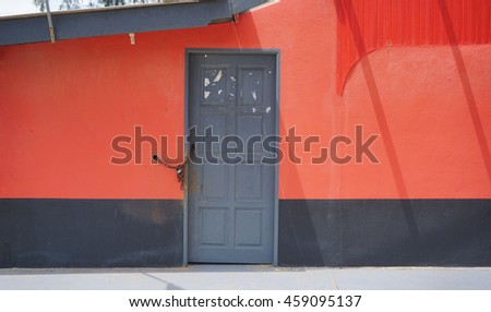Closed grey door on red and wall background - stock photo