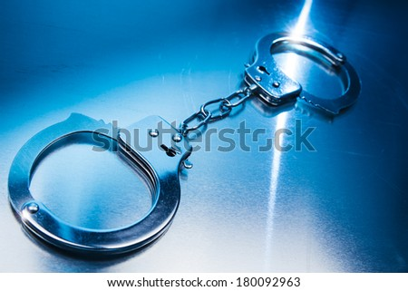 Closed handcuffs, security concept on a metallic background and dramatic lighting - stock photo