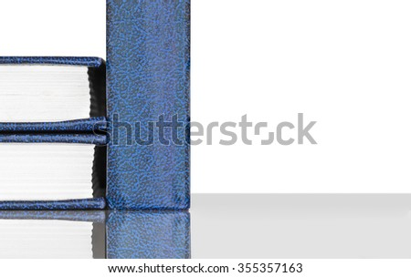 Closed hardcover books with reflection. Low angle view. One book standing and two books on side laying on gray reflective surface. Blue and black textured cover.Isolated on white background,copyspace  - stock photo