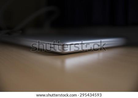 Closed laptop on woorden table - stock photo