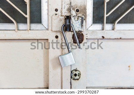 Closed lock on an old metal fence - stock photo