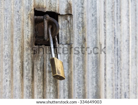 Closed  metal lock to old zinc door for security protection  - stock photo