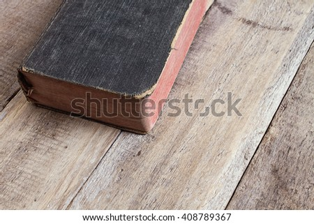 closed old book on old wooden table - stock photo