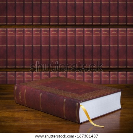 Closed old book with blank hardcover on the table and bookshelf in the background - stock photo
