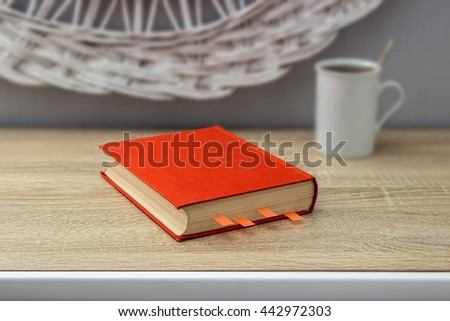 Closed orange book with bookmarks. White ceramic cup of tea in the background. Reading, learning, close-up. - stock photo
