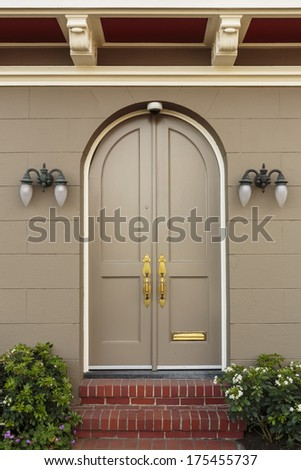 Closed ornate wood door of an upscale home, accented with an iron barred window, iron door knocker, and iron bolts. The door is set into a beige stucco house, framed with a wide arch and planters. - stock photo