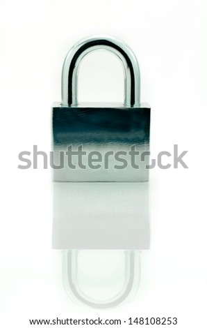 Closed padlock with key on a white background with reflections - stock photo