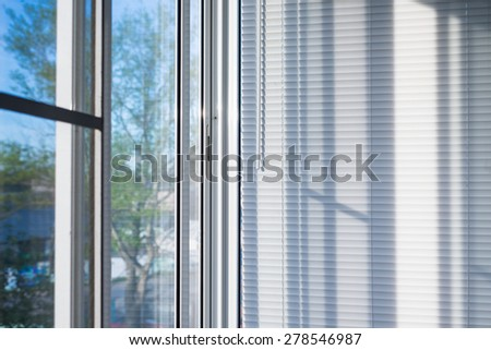 closed plastic blinds on the window with the reflection in the glass - stock photo