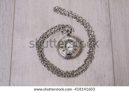 closed pocket watch lying on a light wooden background - stock photo
