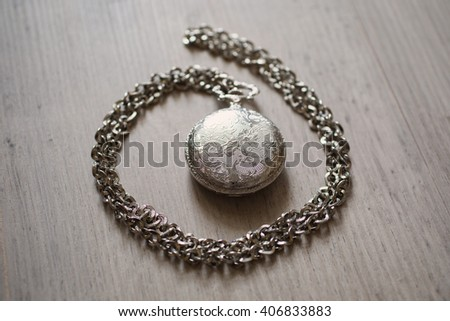 closed pocket watch lying on a light wooden background, metal vintage pocket watch on a metal chain, retro style  - stock photo