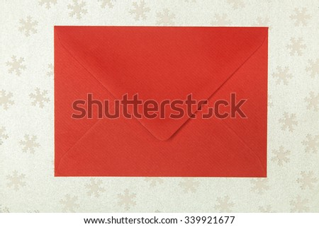 closed red envelope on snowflakes background, christmastime - stock photo